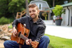 Charlotte musician Seth Pittman holding guitar